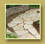 Gorgeous flagstone path beside stone wall and maroon astilbe