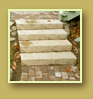 Cobblestone style pavers lead up stone stairs and past a tiny round patio